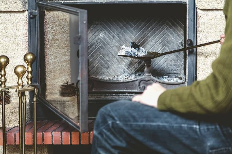 Hombre limpiando chimenea con pala