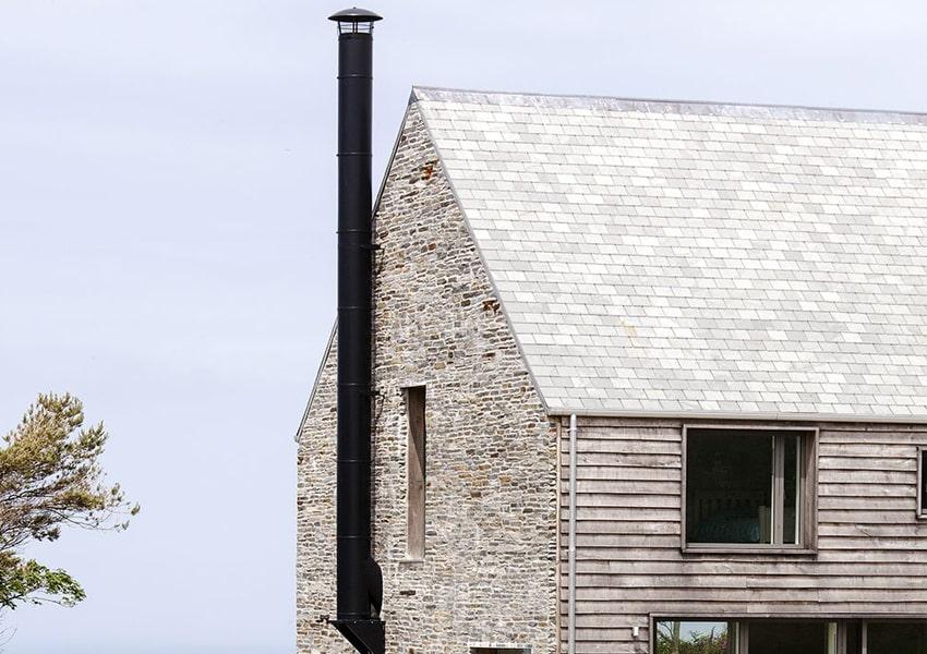 Chimenea solar instalada en casa de madera y ladrillo