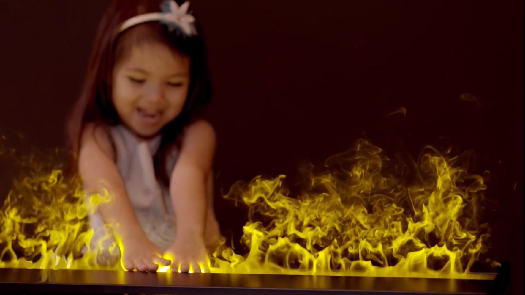 Niña tocando el fuego sin quemarse