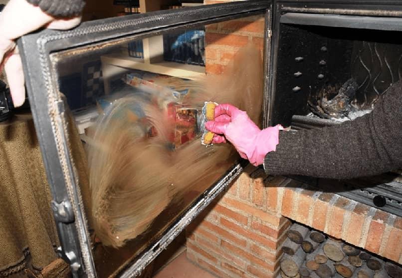 Hombre limpiando el cristal de una chimenea cerrada